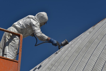Tradesman spray painting the roof of an industrial building Stok Fotoğraf - 27940332