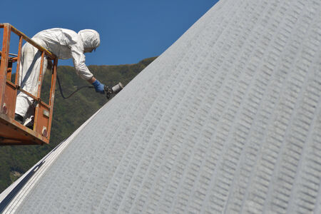 Tradesman spray painting the roof of an industrial building photo