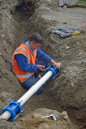 Plumber tightens the joiners on pipes for a broken stormwater drainage system photo