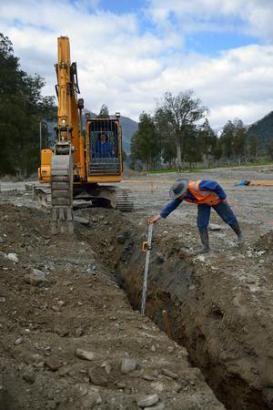 商人は新しい雨水排水の深さをチェックします。