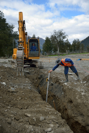 A tradesman checks the depth of a new stormwater drain Stock Photo