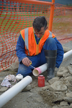 trenching: A plumber joins new pipes for a stormwater drain