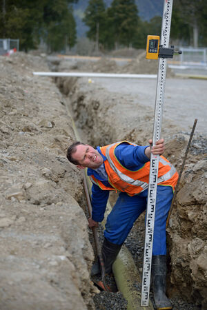 trenching: A tradesman adjusts the depth of his pipe in a new stormwater drain Stock Photo