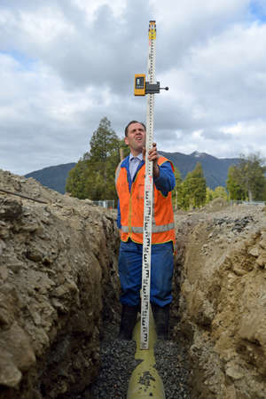 trenching: A tradesman checks the depth of a new stormwater drain Stock Photo