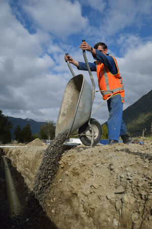 A tradesman tips gravel into a new stormwater drain