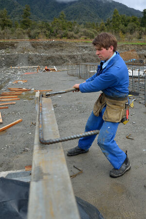 A builder bends reinforcing steel for foundations work on a large construction project