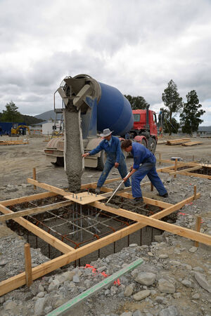 Builder directing wet concrete into foundations of a large building