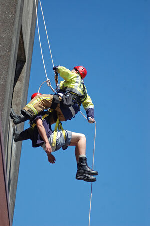 abseil: GREYMOUTH, NEW ZEALAND,  CIRCA 2006: rescue fireman abseils down the outside of a building with a patient in a rescue harness