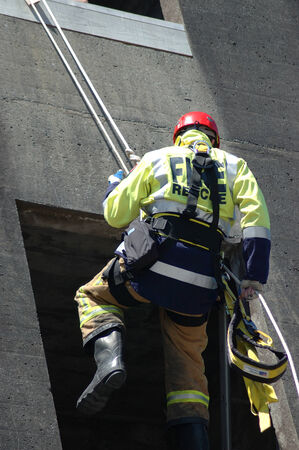 abseiling: rescue fireman abseiling down the outside of a building