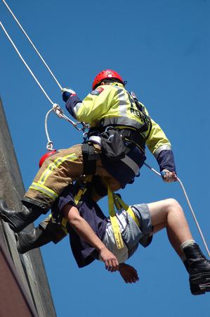 abseilen: Greymouth, Neuseeland, CIRCA 2006: Feuerwehrmann seilt Rettungs an der Au�enseite eines Geb�udes mit einem Patienten in einem Rettungsgurt Editorial