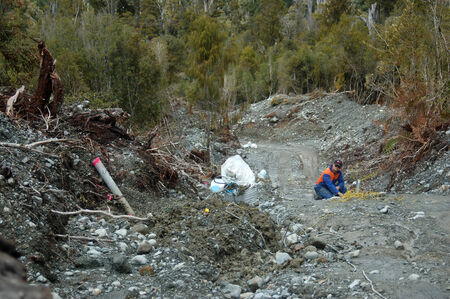settling: Man blows up a 4 metre deep charge for seismic test, Westland, New Zealand. The ground around the pipe is now settling.