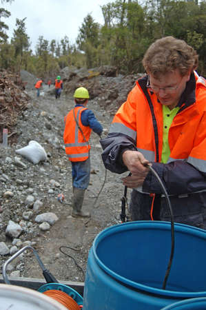 seismic: Men collect in microphone cables used for seismic test, Westland, New Zealand.