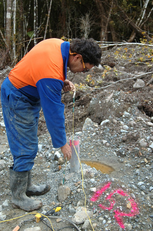 seismic: Man connects up cable for seismic test, Westland, New Zealand. The PVC pipe contains the explosive 4m down. Stock Photo