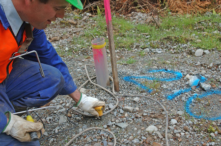 seismic: Man places geophone in ground at hole 210 for seismic test, Westland, New Zealand