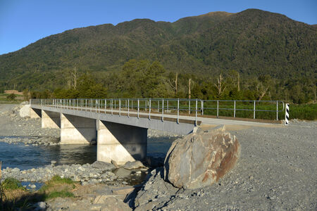 completed concrete bridge over a small river in Westland, New Zealand