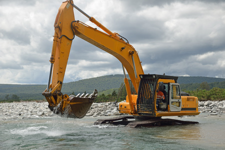 westland: 10 ton digger shifting shingle to deepen the channel in a flowing river, Westland, New Zealand