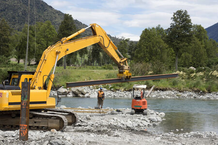 A digger brings another steel pylon into place during construction of a concrete bridge over a small river in Westland, New Zealand