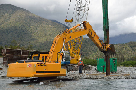 Builders use a digger to straighten the pylons for a concrete bridge over a small river in Westland, New Zealand