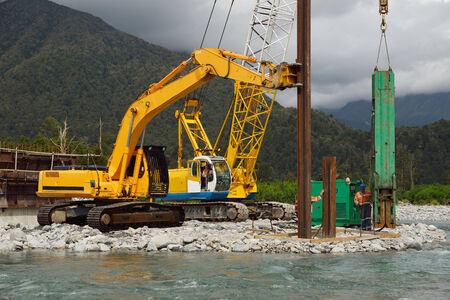 Builders drive pylons for a concrete bridge over a river in Westland, New Zealand