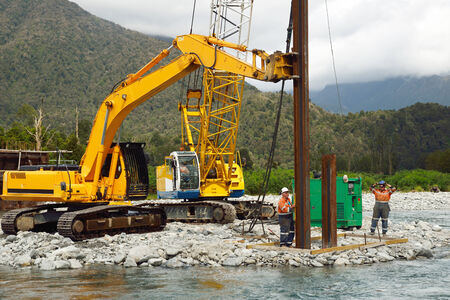 Builders drive pylons for a concrete bridge over a small river in Westland, New Zealand photo