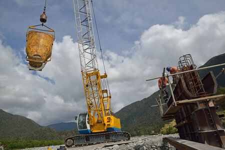 A crane driver swings across a bucket of cement for builders pouring a pylon for a concrete bridge over a small river in Westland, New Zealand