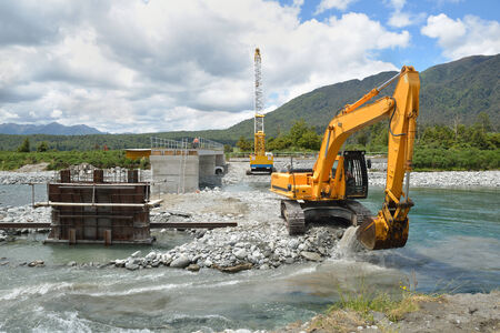 Builders create a new channel to control the river while they construct a concrete bridge over a small river in Westland, New Zealand