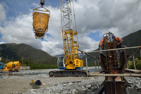 westland: Builders construct a concrete bridge over a small river in Westland, New Zealand