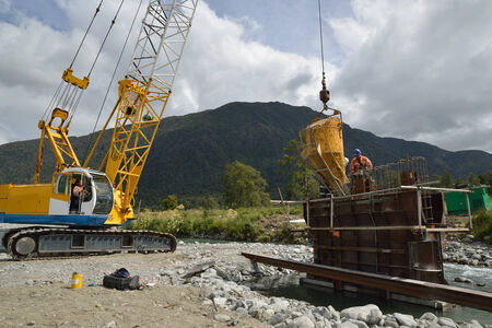 Builders pour concete into the pylon of a concrete bridge over a small river in Westland, New Zealand