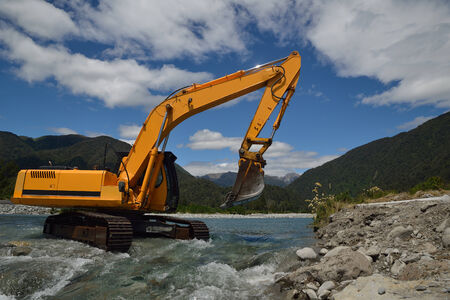 earth moving equipment: digger shifting shingle to deepen the channel in a flowing river, Westland, New Zealand