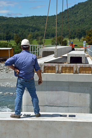 Builders construct a concrete bridge over a small river in Westland, New Zealand