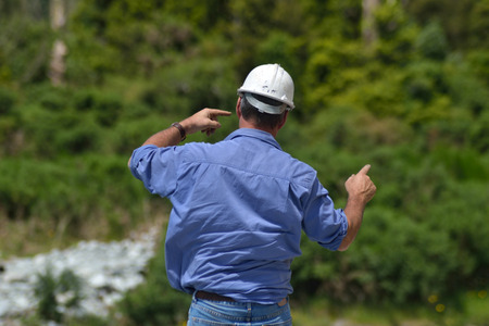 Building foreman instructs his crane driver while constructing a concrete bridge over a small river in Westland, New Zealand