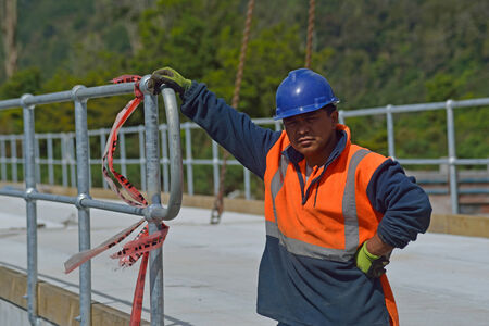 westland: Portrait of builder on a bridge-building site at a small river in Westland, New Zealand