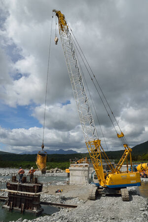 GREYMOUTH, NEW ZEALAND, DECEMBER 2013: Builders construct a concrete bridge over a small river in Westland, New Zealand