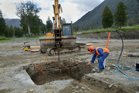 A builder directs a cage of reinforcing rods into the foundation for a portal a large building Banco de Imagens