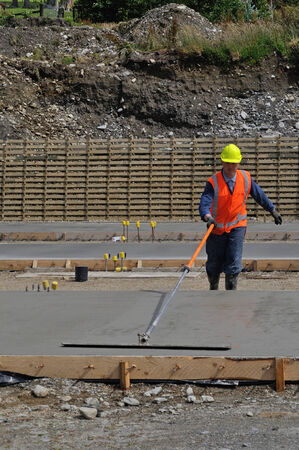 A builder uses a long handled trowel to float off a wet concrete slab for a large building