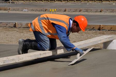 A builder uses a wooden trowel to float off a wet concrete slab for a large building Banco de Imagens