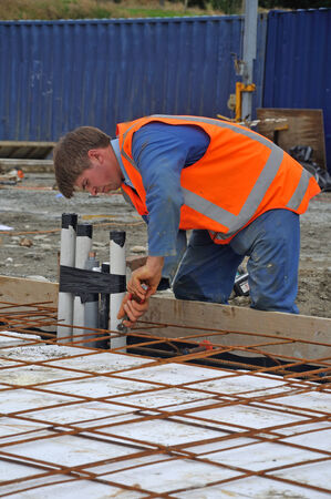 A builder ties off the reinforcing before concrete is poured into the foundations of a large building