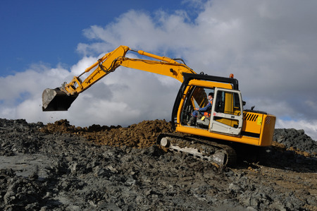 effluent: A 10 ton digger shifts clay for lining a dairy effluent pond, Westland, New Zealand