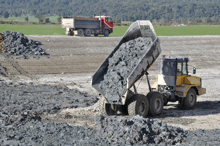 effluent: A dumpster delivers more clay for lining a dairy effluent pond, Westland, New Zealand
