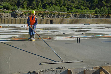 A builder floating off new concrete for a large building near Greymouth, South