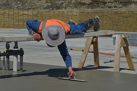 sawhorse: A builder uses a sawhorse and plank to position himself while floating off new concrete for a large building near Greymouth, South Island, New Zealand