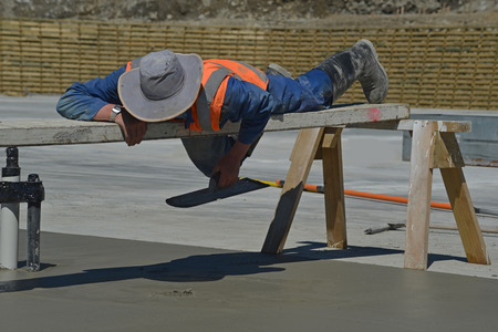A builder uses a sawhorse and plank to position himself while floating off new concrete for a large building near Greymouth, South Island, New Zealand