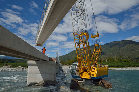 laboring: Builders construct a concrete bridge over a small river in Westland, New Zealand