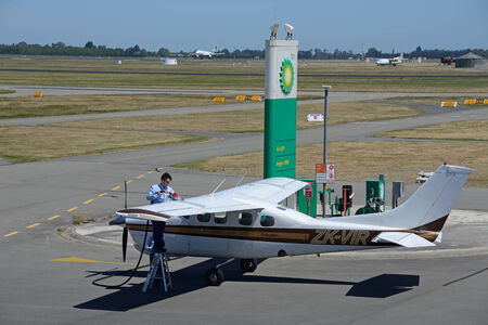 fixed wing aircraft: CHRISTCHURCH, NEW ZEALAND, DECEMBER 12, 2014: The unidentified pilot of a light plane refuels his plane at Christchurch International Airport on December 12, 2014 Editorial