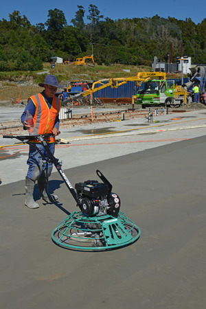GREYMOUTH, NEW ZEALAND, JULY 16, 2014: A builder uses a mechanical float to smooth new concrete for a large building near Greymouth, South Island, New Zealand.