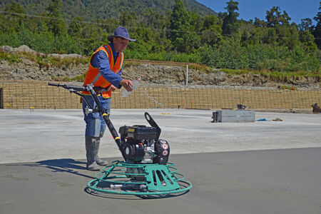 GREYMOUTH, NEW ZEALAND, FEBRUARY 2, 2014: A builder wets the concrete while he uses a mechanical float to smooth new concrete for a large building near Greymouth, South Island, New Zealand.