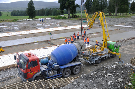 GREYMOUTH, NEW ZEALAND, JANUARY 2014: A team of builderas gather to spread concrete for the slab of a large building, Editorial