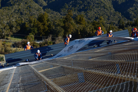 GREYMOUTH, NEW ZEALAND, SEPTEMBER 6, 2014: A team of contractors put the roof on a large commercial building near Greymouth, New Zealand, September 6, 2014 Editorial
