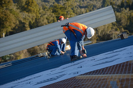 rafter: GREYMOUTH, NEW ZEALAND, SEPTEMBER 6, 2014: A team of contractors put the roof on a large commercial building near Greymouth, New Zealand, September 6, 2014