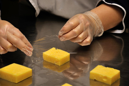 A caterer wraps pieces of cheese for guests at a reception